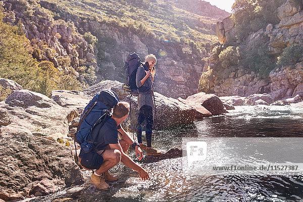 Junges Paar mit Rucksäcken beim Wandern  Spritzwasser am Bach
