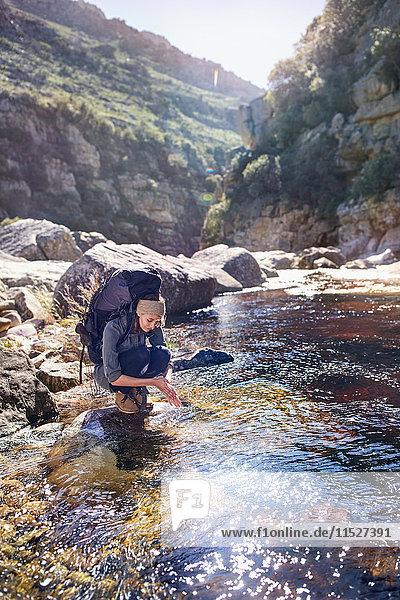 Junge Frau mit Rucksackwandern  Händewaschen am sonnigen Bach
