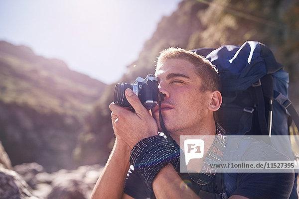 Junger Mann mit Rucksackwandern und Fotografieren mit Kamera