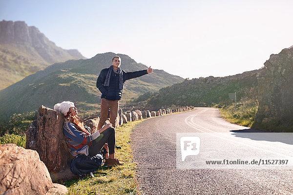 Junges Paar trampen am sonnigen  abgelegenen Straßenrand