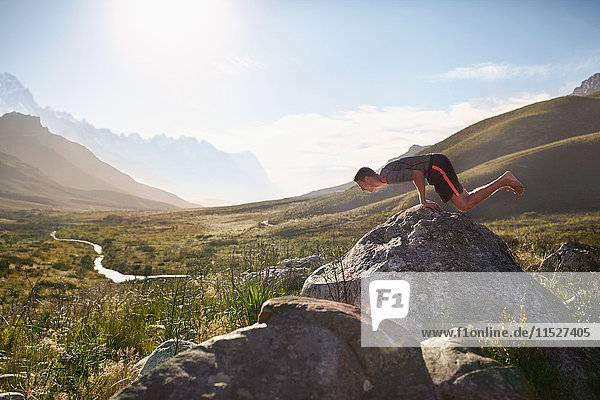 Young man balancing on hands on rock in sunny  remote valley