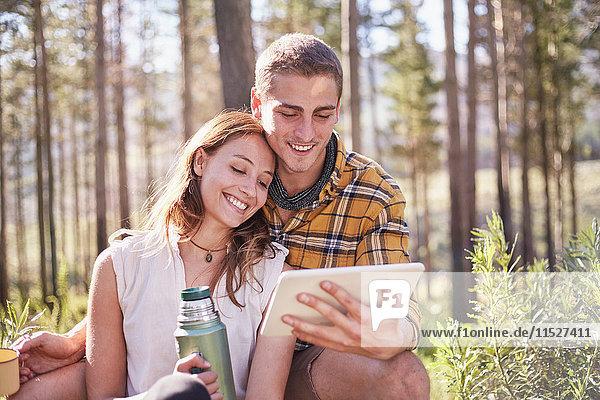 Junges Paar zelten  Kaffee trinken und digitales Tablett in sonnigen Wäldern benutzen