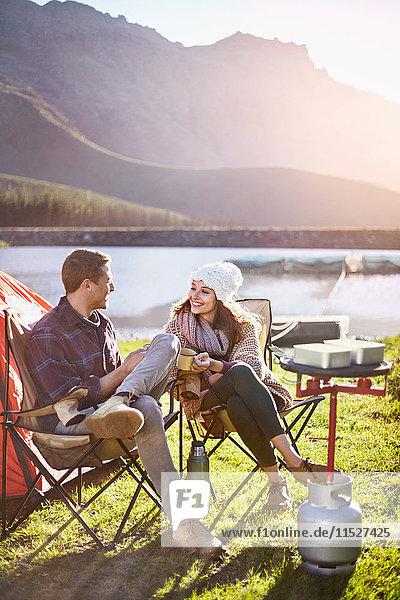 Junges Paar zelten  Kaffee trinken auf dem sonnigen Campingplatz am Seeufer