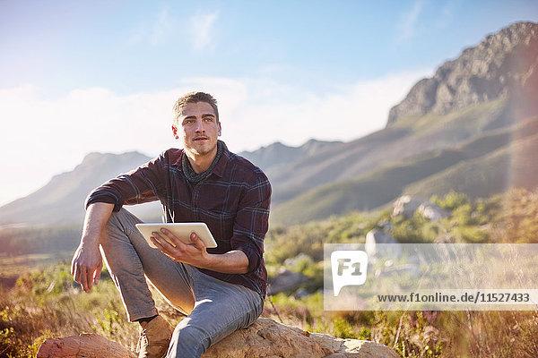 Junger Mann mit digitalem Tablett auf Felsen im sonnigen  abgelegenen Tal