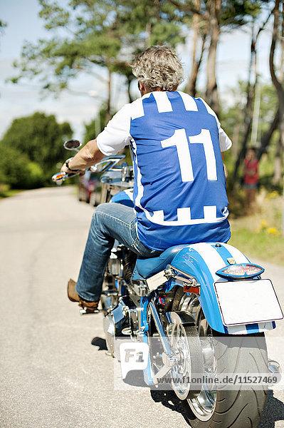 Senior man riding motorcycle  rear view