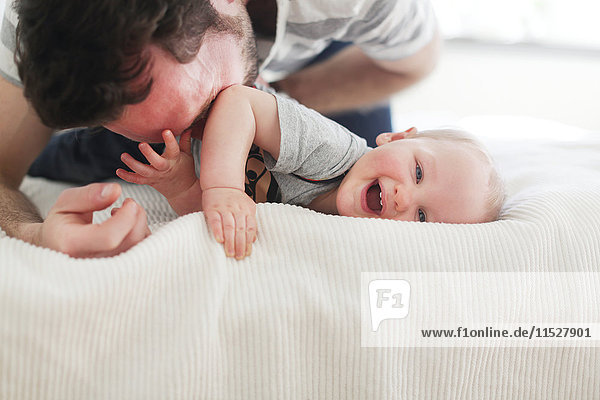 Father playing with son on bed