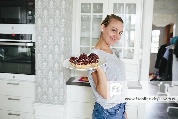 Smiling woman holding snacks on plate