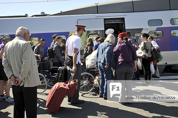 France  Loire-Atlantique  railway station of Nantes city  travelers boarding a high-speed train  SNCF employees helping disabled people carrying their luggage