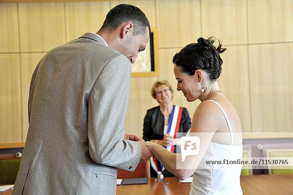 Frankreich  Westfrankreich  Hochzeit eines jungen Ehepaares Mannes im Rathaus von Saint-Gilles-Croix-de-Vie  Bürgermeister mit französischem dreifarbigem Schal  Ringtausch  Heirat.