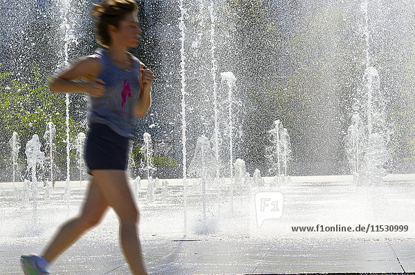 France  Paris 15th district  Parc Andre Citroen. Woman running in front of the water jets