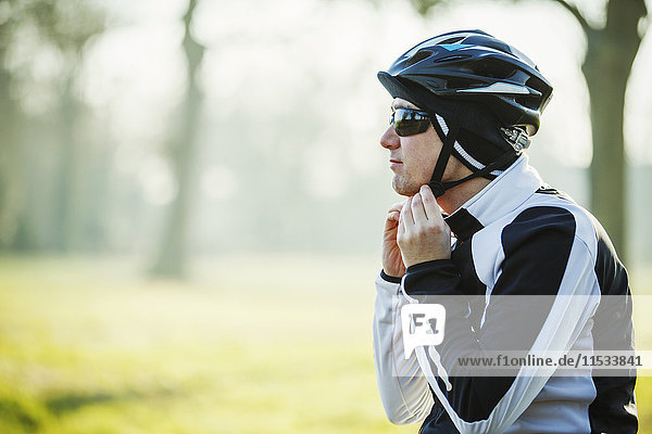 A cyclist adjusting the chinstrap on his helmet.