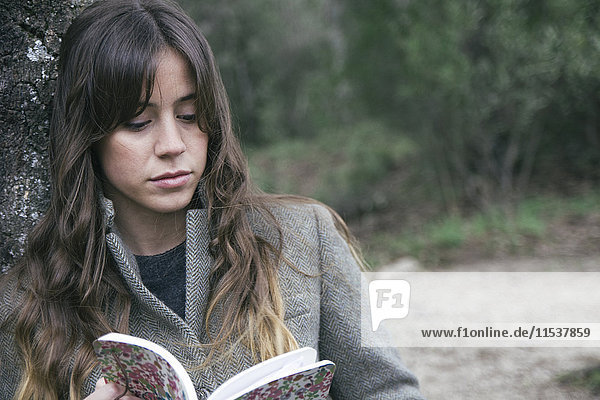 Young woman reading a book leaning against a cork oak tree