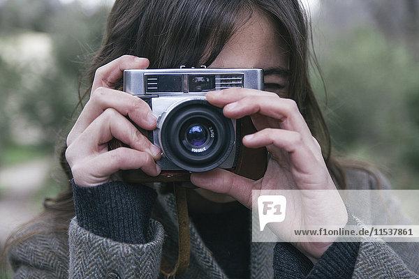 Frau fotografiert mit einer analogen Kamera