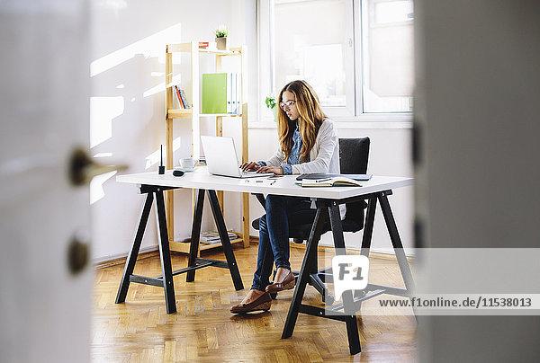 Junge Frau bei der Arbeit mit dem Laptop im Home-Office