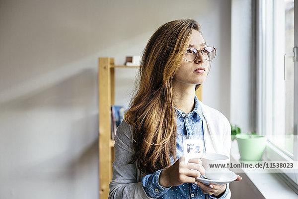 Junge Frau ruht sich bei einer Tasse Kaffee aus und schaut durchs Fenster in ihr Home-Office.
