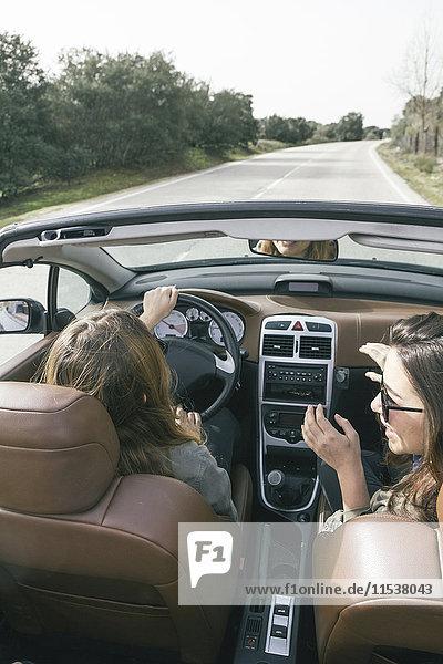 Frau fährt ein Cabriolet mit ihrer Freundin auf dem Beifahrersitz.