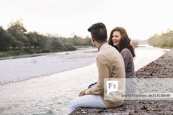 Italien  Belluno  junges Paar vor einem Fluss sitzend