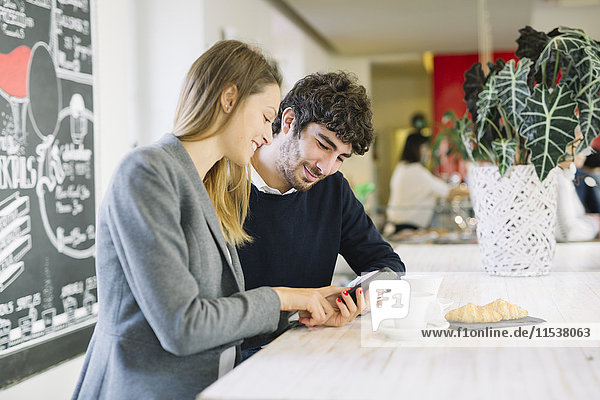 Zwei Kollegen in einem Café beim Blick auf das Handy