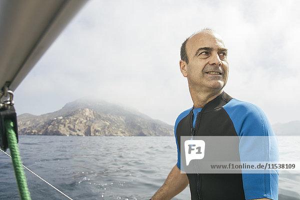 Mann segelt mit seinem Segelboot auf See