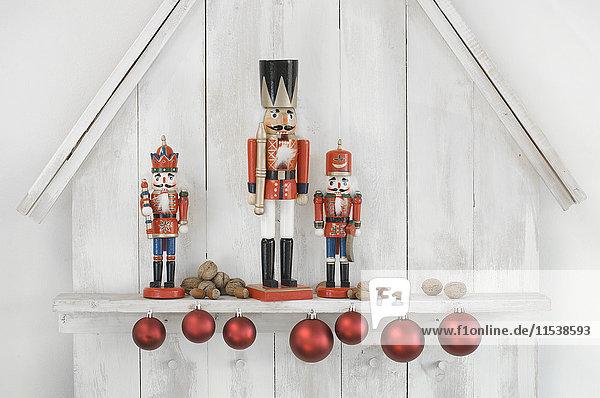 Weihnachtsdekoration mit drei Nussknackern  Weihnachtskugeln und Nüssen