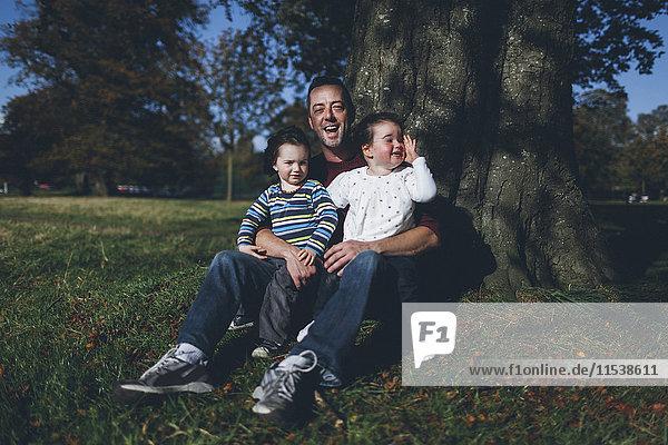 Vater und seine Kinder an einem Baum sitzend