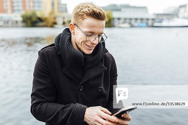 Irland  Dublin  lächelnder junger Mann mit Blick auf sein Smartphone vor dem Wasser