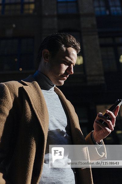 Mann auf dem Handy in der Stadt