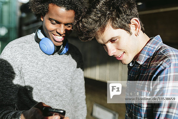 UK  London  two young man looking at theit smartphones