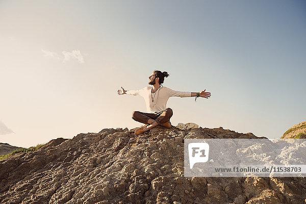Mann sitzt auf einem Hügel mit ausgestreckten Armen und gekreuzten Beinen.