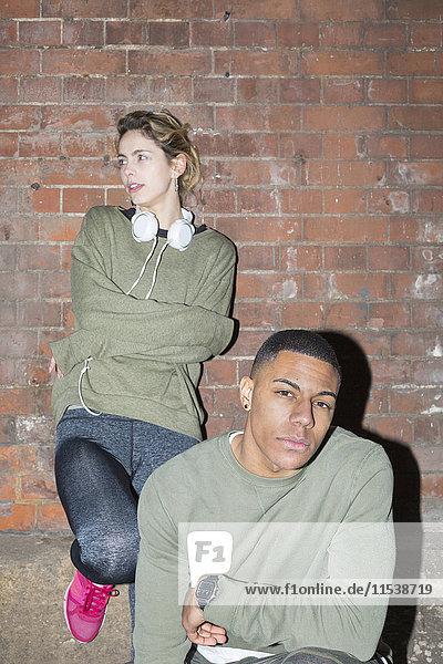 Stilvolles junges Paar an der Backsteinmauer bei Nacht