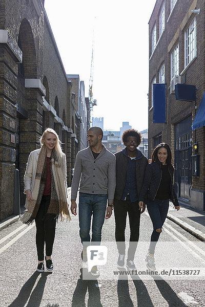 Gruppe von Freunden  die auf der städtischen Straße spazieren gehen
