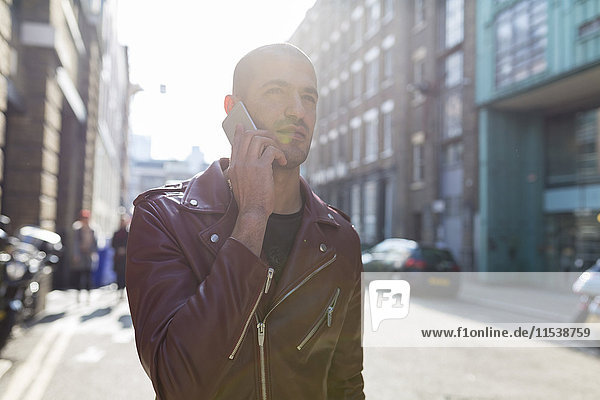 Young man on cell phone on urban street