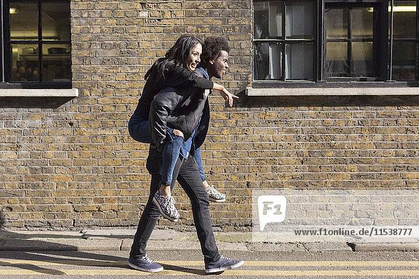 Junger Mann mit Freundin Huckepack im Backsteingebäude