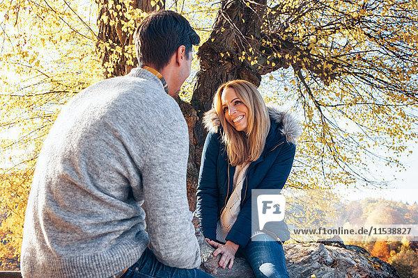Glückliches Paar genießt den Herbst im Wald auf dem Baumstamm