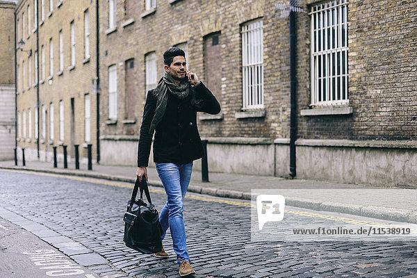 Junger  lässiger Geschäftsmann  der mit dem Handy auf der Straße unterwegs ist.