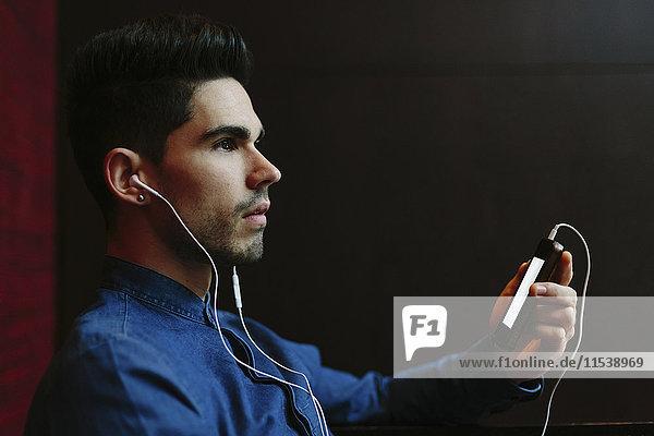 Profil eines jungen Mannes  der Musik mit Kopfhörern vor schwarzem Hintergrund hört.