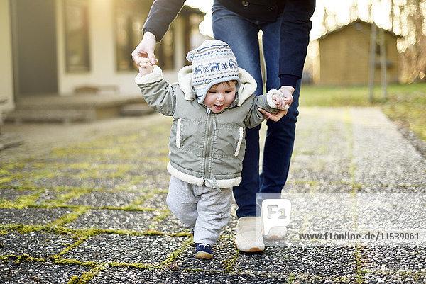 Kleines Mädchen  das mit Hilfe seiner Mutter laufen lernt
