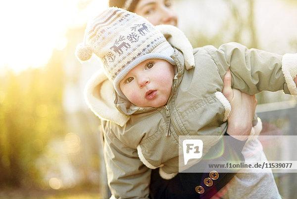 Porträt eines Mädchens  das am Arm seiner Mutter hält
