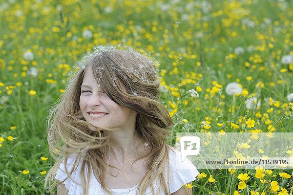 Porträt eines lächelnden Mädchens mit Löwenzahnsamen auf dem Haar