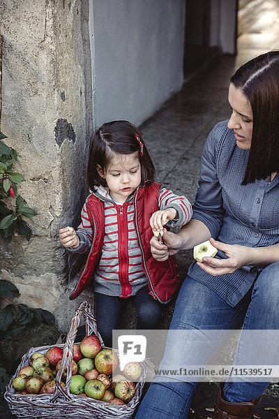 Mutter und ihre kleine Tochter mit frisch geernteten Bio-Äpfeln Mutter und ihre kleine Tochter mit frisch geernteten Bio-Äpfeln