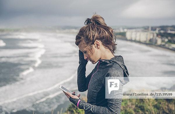 Porträt einer sportlichen Frau mittlerer Größe mit Smartphone