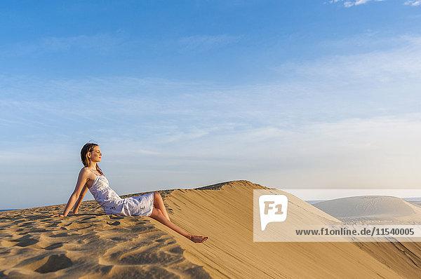 Frau auf Düne sitzend  nachdenkend