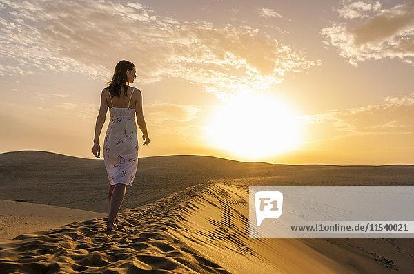 Frau geht auf Düne