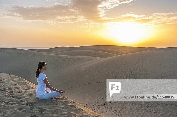 Frau praktiziert Yoga auf Sanddünen