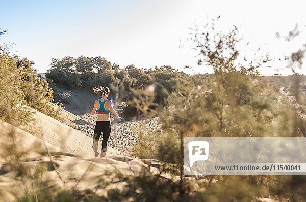 Frau läuft in den Dünen