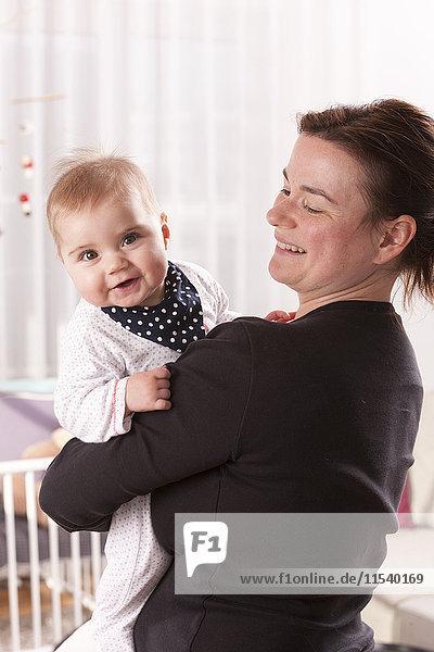 Glückliches kleines Mädchen auf den Armen der Mutter