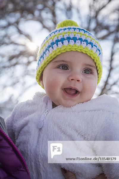 Portrait of happy baby girl wearing bobble hat