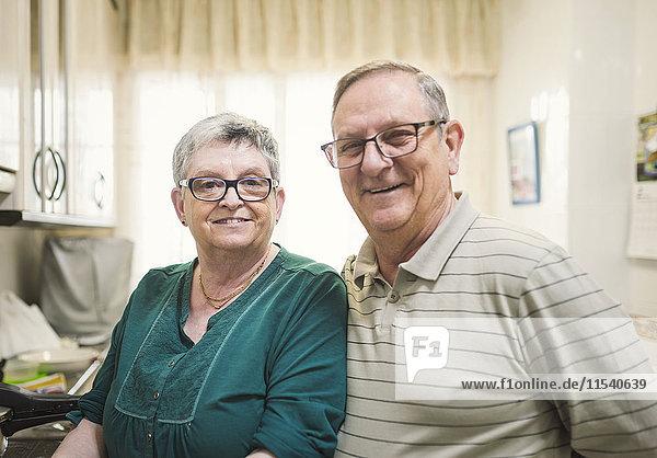 Portrait of confident senior couple at home