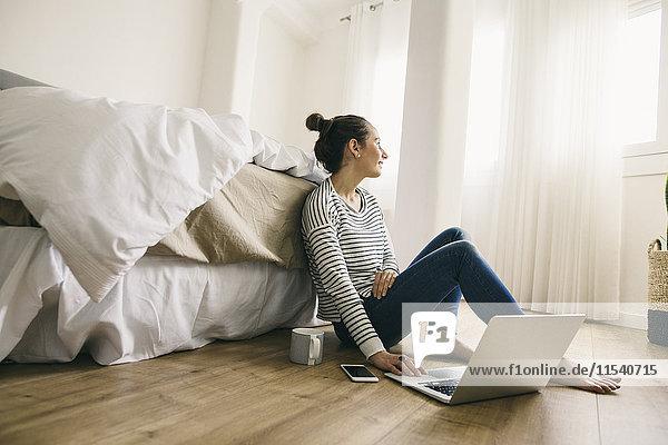 Entspannte Frau sitzt im Schlafzimmer mit Laptop