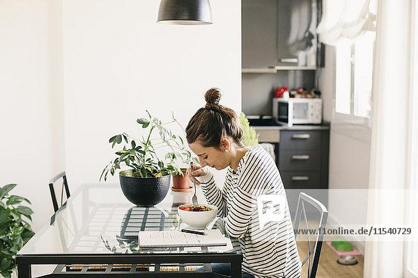 Frau am Tisch sitzend mit Obstmüsli und Blick auf den Notizblock